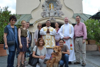 group posing with dog and religious men