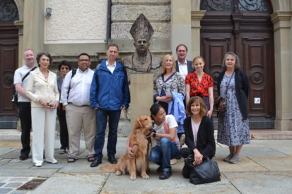 group posing with pope statue and dog