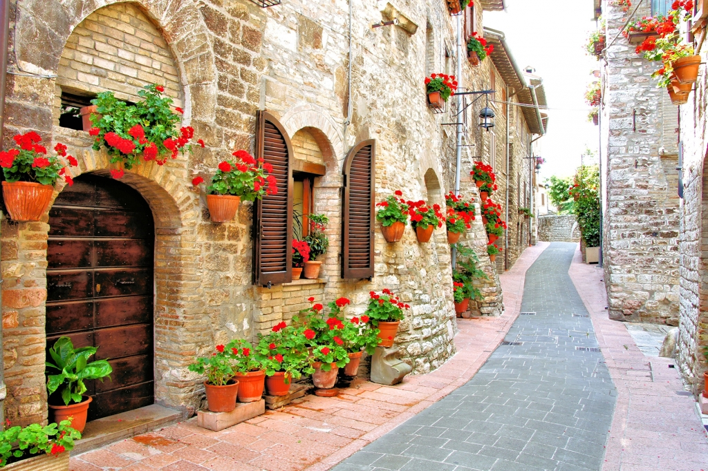 narrow streets of hill town in italy filled with flowers